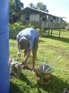 Repairing water collection tanks in Pedro's village
